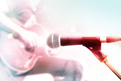Abstrakt färgrik mikrofon med gitarristen på etappen, pastellfärgad färg Arkivbilder