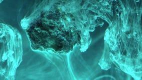 Abstrakt flödande färgpulver i vatten med stenen