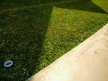 Abstrakt form av ljus och skuggor på trottoarer och grässlätten, triangulära former, ljus solig dag arkivfoton