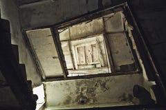 Abstrakt foto av den mörka trappuppgången i form av tunnelen eller mörkerkorridoren i övergiven byggnad Royaltyfri Foto