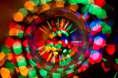 Abstrakt foto av oskarpa ljusa källor av olika färger som vrids in i en cirkel royaltyfri bild