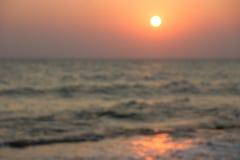 Abstrakt foto av stranden på solnedgången, ut ur fokussolen och havet, suddig bakgrund Royaltyfri Bild