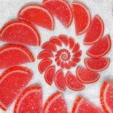 Abstrakt fruktgelé kilar den röda cantlelobulen på bakgrund för vitt socker göra gelé av red Abstrakt fruktgelé på backgrou för v Arkivbilder