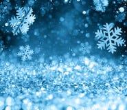Abstrakt glödande blå bakgrund för jul med snöflingor Arkivbild