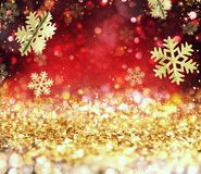 Abstrakt glödande julguld och röd bakgrund med snöflingor Royaltyfri Fotografi