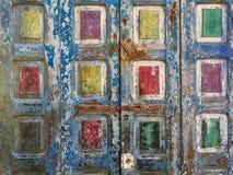 Abstrakt grungebakgrund med fyrkanterna av guling, gräsplan, röd färg på en gammal träyttersida av blått Arkivfoto
