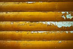 Abstrakt grungebakgrund med träbräden som är dolda med gul målarfärg, som med rätsidan faller av och utsatt för att slösa Arkivbilder