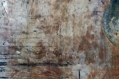 Abstrakt grungebakgrundstextur av ett metallark med grova slaglängder av brun målarfärg och en fläck av grön målarfärg i övrerigg Royaltyfri Foto