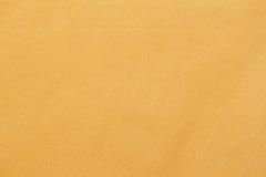 Abstrakt gul tygtexturbakgrund med kopieringsutrymme för text eller bild Arkivbilder
