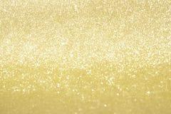 Abstrakt guld blänker bokehljus med mjuk ljus bakgrund royaltyfri foto