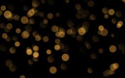 Abstrakt guld- glänsande bokeh som isoleras på svart bakgrund Garnering- eller julbakgrund royaltyfri illustrationer