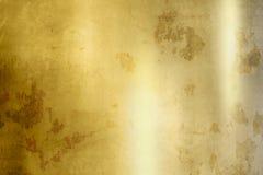 Guld- bakgrund - grunge texturerar Arkivbild