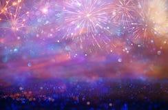 Abstrakt guld och lilor blänker bakgrund med fyrverkerier julhelgdagsafton, 4th av det juli feriebegreppet Arkivfoton