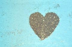 Abstrakt hjärta av guld- blänker mousserar på blå bakgrund Arkivfoton