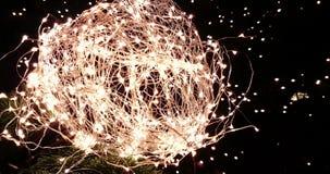 Abstrakt jul blänker ljus klumpa ihop sig på xmas-träd med varm gnistrandebokeh på svart bakgrund, begrepp av guld- feriexmas stock video