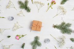 Abstrakt julbakgrund dekorerade med gåvan i mitt och xmas-beståndsdelar - kottar, trädfilialer, rosor på en vit träbaksida royaltyfria foton