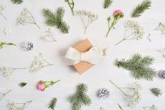 Abstrakt julbakgrund dekorerade med gåvan i mitt och xmas-beståndsdelar - kottar, trädfilialer, rosor på en vit träbaksida arkivbild