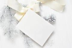 Abstrakt julbakgrund, vitt ark av papper som ligger bland små garneringar på det vita träskrivbordet Lekmanna- modell för lägenhe royaltyfri bild