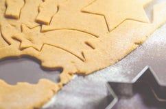 Abstrakt julmatbakgrund med kakaformer och mjöl Stekheta julkakor - tabell, kakaskärare och kakor Fotografering för Bildbyråer