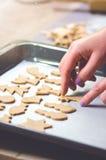 Abstrakt julmatbakgrund med kakaformer och mjöl Stekheta julkakor - tabell, kakaskärare och kakor Royaltyfria Bilder