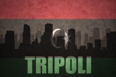 Abstrakt kontur av staden med text Tripoli på den libyska flaggan för tappning Royaltyfria Bilder