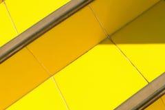Abstrakt ljus bakgrund - trappa av keramiska tegelplattor av varm guling som är upplysta vid solen med gjorda mörkare hörn Arkivbilder