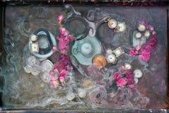 Abstrakt ljus stilleben med mozhsnitsy, klockan och karmosinröda blommor i vatten med vita skilsmässor, modern inredesign av Arkivbild