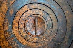 Abstrakt metallbakgrund med geometriska hål i en cirkel och textur rostar apelsin-brunt med fläckar Arkivfoton