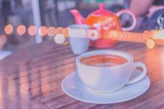 Abstrakt mjuk suddig och mjuk fokus per koppen av cappuccino, varmt kaffe med bokehen, strålljus, bakgrund för signal för linssig royaltyfria foton