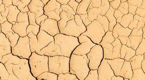 Abstrakt modelllinje av naturlig sprucken jordning i bygd med ljus - brun textur för jordfärgbakgrund Fotografering för Bildbyråer