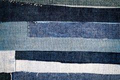 Abstrakt olik bakgrund för jeansbandtextur arkivbilder