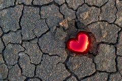 Abstrakt röd hjärtaform på sprickajordnatursolnedgången royaltyfria foton
