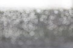 Abstrakt regndroppe och bokeh på vindrutan, suddighet, vit backgroun Arkivfoto