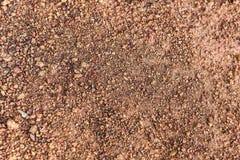 Abstrakt sammansättning av rött grus med ris arkivfoto