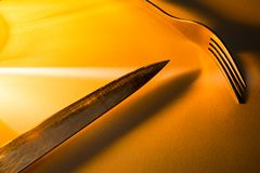 Abstrakt sammansättning med en kniv och gaffel med varmt gult ljus Arkivbild