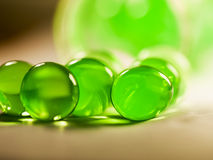 Abstrakt sammansättning med härligt, gör grön, rundar gelébollar på en aluminium folie med reflexioner Arkivbilder