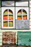 Abstrakt sammansättning med trärundade fönster, den rostiga metallplattan och färgade gardiner med solen tänder Royaltyfria Bilder