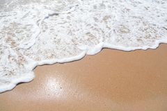 Abstrakt sand av stranden och den mjuka vågen Arkivfoto