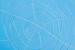 Abstrakt spiderweb, vit dragar på blå bakgrund Arkivbilder