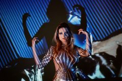 Abstrakt stående av en härlig flicka i ljuset av projektorn Atmosfären av disko 80 x Guld- paljetter A Royaltyfri Foto