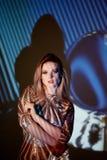 Abstrakt stående av en härlig flicka i ljuset av projektorn Atmosfären av disko 80 x Guld- paljetter A Arkivbilder