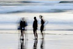 Abstrakt suddig grupp människor på en strand royaltyfria bilder