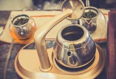 Abstrakt suddig kokkärl och ett exponeringsglas av te i coffee shop Arkivbilder