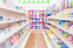 Abstrakt suddig supermarketgång med färgrika hyllor och oigenkännliga kunder som bakgrund Royaltyfria Bilder