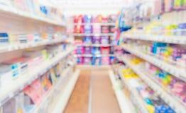 Abstrakt suddig supermarketgång med färgrika hyllor och oigenkännliga kunder som bakgrund Royaltyfri Bild