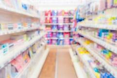 Abstrakt suddig supermarketgång med färgrika hyllor och oigenkännliga kunder som bakgrund Royaltyfria Foton