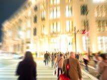 Abstrakt suddighet: folket skynda sig till över vägen med högt byggande f Royaltyfria Foton