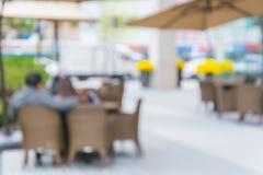 Abstrakt suddighetstabell och stol med den utomhus- uteplatsen för paraply Arkivbild