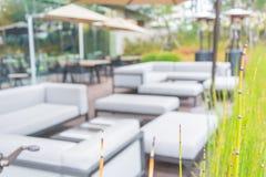 Abstrakt suddighetstabell och stol med den utomhus- uteplatsen för paraply Arkivfoto