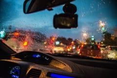 Abstrakt suddigt regn tappar på det glass fönstret för bilen med bokehtrafikljusbakgrund Royaltyfri Fotografi